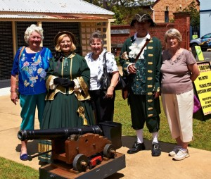 Margaret, Dorothy and Nola helping the town crier prepare the cannon for the midday firing.