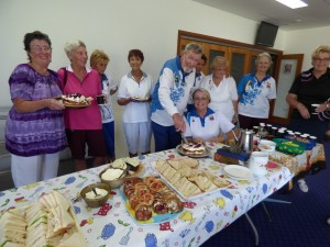Mick cutting his cake at the ladies social day, with President Judy Hammond (kneeling) offering advice and lady bowlers supervising