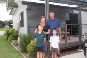 Melanie and Steve May with sons Thomas and Jackson outside one of their cabins, growing in number at the Tin Can Bay Tourist Park