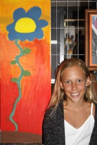 Emma Worthington with her floral art at Brushes by the Sea, the annual art show in Rainbow Beach