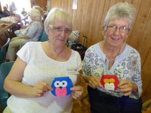 Jacki Cross and Bev Phillips with the their owl purses made in felt