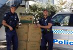 Local officers Mike Brantz and Mick Emery get ready to distribute the anti-domestic voilence coffee cups