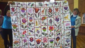 Michelle Mummery helps hold up Beryl Vickery's (pictured right) beautiful garden quilt