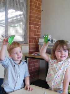 Fletcher and Scarlett hold up their recycled craft at Tin Can Bay Library
