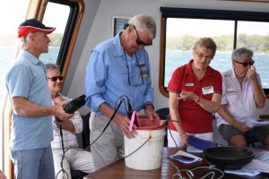 Tin Can Bay waterwatchers, Alan Jones with Bill and Jenny Adamson enjoy the end of year cruise