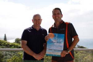 Mark Beech from Rainbow Ocean Palms Resort and Heatley Gilmore from Rainbow Getaway Holiday Apartments show off Rainbow Beach's publication for New Zealand, called Visit Rainbow Beach
