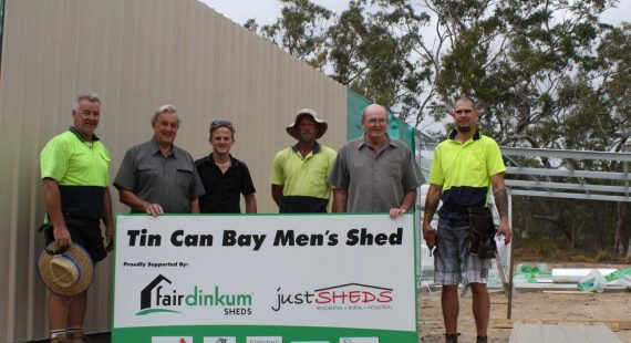 Holding the sign are Brian Linfield and Jamie Barnes form the Tin Can Bay Mens Shed, they are delighted to have the Just Sheds team on site