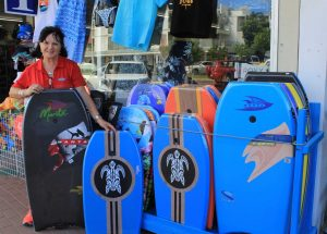 Deb O'Donnell shows off the body boards at 7th Wave Epic Ocean Adventures is also a great spot for shopping and Ola Gunzel will help you find a present - perhaps a surfboard?