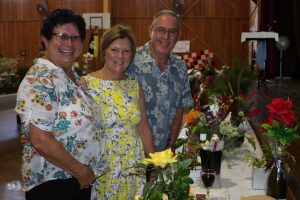 """Judy Cantrell, Maree and Phil Heron discuss the themed displays - spotting""""Days of Wine and Roses"""" and the """"Yellow Rose of Texas"""""""