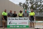 Holding the sign are Brian Linfield and Jamie Barnes from the Tin Can Bay Men's Shed; they are delighted to have the Just Sheds team on site