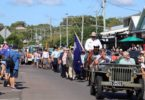 A large crowd waved flags as the Anzac Day March progressed through the main street