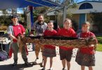 Ty-reece, Brent Miller (presenter), Allyra, Elsie and Alyssa hold a traditional canoe during NAIDOC celebrations last month