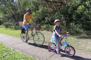 Grant Phelan and daughter Isabel ride home from school