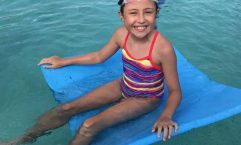 Ella relaxes after some racing and fun during Little Kickers before school, at the Rainbow Beach Aquatic Centre