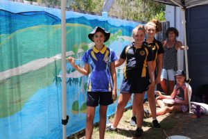 Mrs Lane helps Tia, Janae, Laila and Luxie paint the Police Beat Mural for 2019