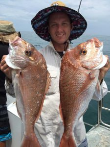 Dan with a pair of snapper with a bagged-out boat