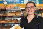 Cleressa Clark of Rainbow Beach holds the famous corn beef and white sauce pie from Ed's Beach Bakery at Rainbow Beach - listed as No. 1 for Top Ten Pies around Australia, by Creek to Coast