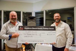 Kroppy handing Shane Handy a cheque for the surf club from the proceeds of the Bull 'n' Bronc