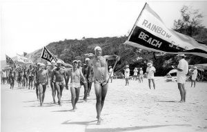 Lofty Wolgast carrying the flag for the club in the first surf carnival ever held at Rainbow Beach in the 1971/1972 season.