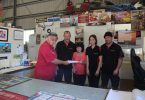 Kim and the crew from Bay Auto at Cooloola Cove presenting Bryan Phillips (Shed Manager) with a cheque for bench sponsorship