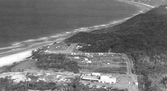 An aerial photo of Rainbow Beach from 1965 showing the Mineral Sands Building, the three mining houses, the Surf Club, Phil Rogers' shop and a few caravans (supplied Garry Hewitt)