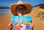 Dr Suzie with her first picture book at Rainbow Beach
