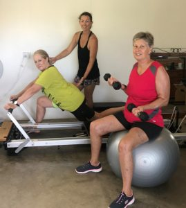 Heather Parker using the Pilates Reformer to release tight areas and strengthen weak places, with Sarah Booth, Pilates and personal trainer, and Lexie Hansen, toning and building strength utilising weights and fitball in the studio