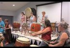 The Japanese Drumming Group with QCWA members, Lorraine and Irene, trying out the drums!