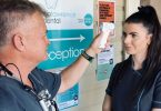 Dr Mark Cull checking Dental Assistant Kym Espin's temperature which is done every day for the patients safety