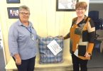 QCWA Tin Can Bay president, Wendy presenting donation to Julia from the Gympie/South Burnett Division President