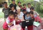 The students of the Cambonian school having their first look at a computer
