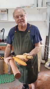 Shed member and lathe master Paul Oliver, showing rolling pins made at the Shed and ready for sale at the TCB Markets