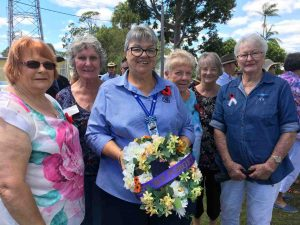 Members of the Tin Can Bay QCWA, Linda, Jill, Wendy, Robyn, Brenda and Dawn with the wreath they presented on Remembrance Day