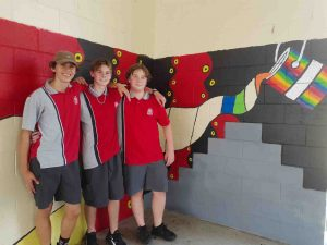 Year 9 students Rakeen, Blake and Mark, who are helping to complete the artwork at the Multi Purpose Space at Tin Can Bay school