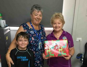 Santa's helper, Steven, Wendy from the CWA and Eileen at the Resource Centre accepting presents