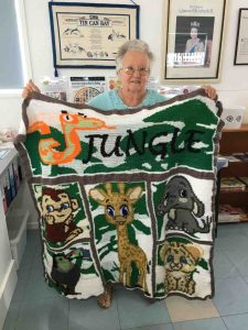 Mollie with her crocheted jungle theme rug, her entry in the QCWA Knitting Competition