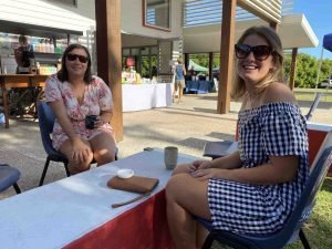 Lovely smiles from Tori McIlroy and Tawney Gilbert, relaxing at the Community Centre Markets, now held on the second Saturday morning every month in Rainbow Beach