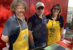 Tin Can Bay Lions Club volunteers Pat Green from Mitre 10, Rob and Ilse Storrie sizzled sausages at the Rainbow Beach Market