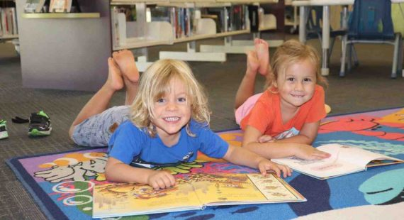 Our libraries have lots on for the school break: Damon and Lelania enjoy a good book at First 5 Forever, Rainbow Beach Library