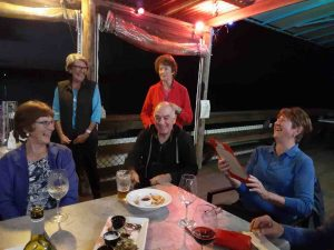 Octogenarian Norma Sanderson celebrating with fellow Dragons and friends at TCB Yacht Club: Andra Casey, Pam Corey, Vic Vella, Elaine Dimmock, and Norma, reading her handmade birthday card