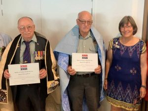Locals, Joe Casey and Barry Hogan, are awarded their handmade quilts by Barbara Kenny of Quilts of Valour